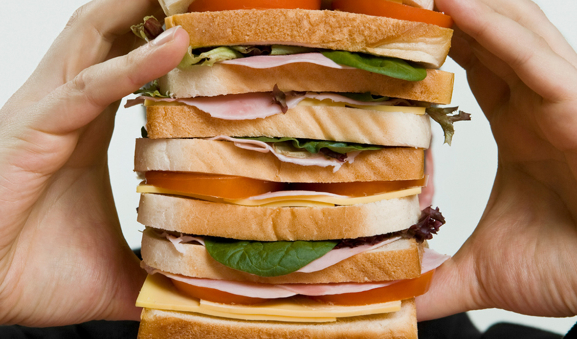 Two hands around a large sandwich with lettuce, tomato, and turkey