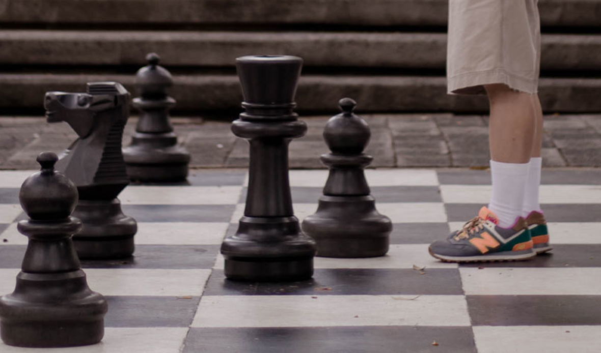 Large chess board with pawns facing human