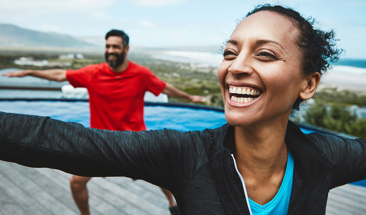 Couple doing yoga outside and smiling